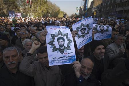 Worshippers carry portraits of Iranian nuclear scientist Mostafa Ahmadi-Roshan, who was killed in a bomb blast in Tehran on January 11, during his funeral after Friday prayers in Tehran January 13, 2012. REUTERS/Morteza Nikoubazl