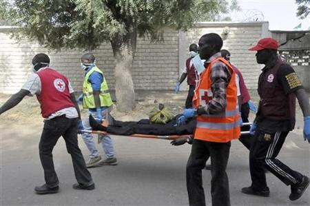 Red Cross officials carry the victim of a bomb attack on a stretcher during an evacuation in Nigeria's northern city of Kano January 21, 2012. REUTERS/Stringer