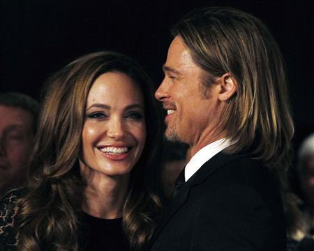 Actress Angelina Jolie smiles with her partner Brad Pitt as they arrive at the 23rd annual Producers Guild Awards in Beverly Hills, California, January 21, 2012. Jolie, who directed and produced the film ''In The Land of Blood and Honey'', and other producers of the film received the Stanley Kramer Award at the event.  REUTERS/Fred Prouser