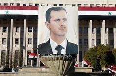"""Портрет сирийского президента Башара Асада на здании ЦБ Сирии во время акции его сторонников в в Дамаске 20 января 2012 года. Власти Сирии в понедельник отвергли план мирного урегулирования ситуации в стране, предложенный в воскресенье Лигой арабских государств и включающий пункт о передаче власти Башаром Асадом вице-президенту и создание правительства национального единства, назвав его частью """"заговора против Сирии"""". REUTERS/Khaled al-Hariri"""