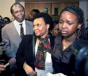 <p>Leon Mugusera (L), along with his wife (C) and daughter (R), walk out of court April 12, 2001 in Quebec City. REUTERS/Didier Debusschere</p>