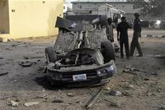 Policemen inspect a bomb site at the police headquarters in Nigeria's northern city of Kano January 22, 2012, after a bomb attack on Friday.  REUTERS/Stringer