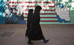 """Женщины проходят мимо антиамериканского граффити на стене бывшего посольства США в Тегеране 12октября 2011 года. Иран обвинил Европу, отказавшуюся накануне от импорта иранской нефти, в развязывании """"психологической войны"""" и снова пригрозил перекрыть Ормузский пролив, через который проходит значительная часть нефти из стран Персидского залива. REUTERS/Morteza Nikoubazl"""