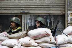 Сирийские военные на КПП в Хомсе 23 января 2012 года. Министры иностранных дел Евросоюза в понедельник ужесточили санкции против Сирии, добавив в список 22 физических и восемь юридических лиц в знак протеста против унесшего тысячи жизней насилия в отношении несогласных с правлением Башара Асада. REUTERS/Ahmed Jadallah