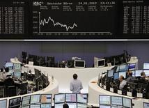 Трейдеры перед электронным табло на Франкфуртской фондовой бирже, 24 января 2012 г. Европейские рынки акций снизились в среду после того, как инвесторы зафиксировали прибыль в банковских акциях, опасаясь, что давление на Европейский Центробанк (ЕЦБ) с требованием списать греческие долги может нарушить его способность скупать гособлигации периферийных стран блока. REUTERS/Amanda Andersen