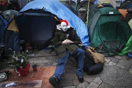 An Occupy London Stock Exchange protestor wears a Santa hat and Guy Fawkes mask while sitting outside a tent on Christmas eve in front of St Pauls Cathedral in London, December 24, 2011. REUTERS/Finbarr O'Reilly