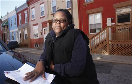Jennifer Wilson, a former nursery school teacher from Philadelphia, poses with bank papers in front of her residence in Philadelphia, Pennsylvania January 20, 2012.   REUTERS/Tim Shaffer