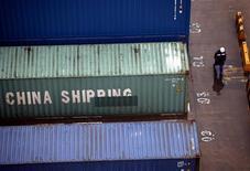 Рабочий шанхайского порта проходит мимо грузовых контейнеров 19 января 2011 года. Магнитогорский металлургический комбинат сообщил, что в 2011 году увеличил выпуск стали на 7 процентов до 12,2 миллиона тонн. REUTERS/Carlos Barria