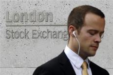 Человек проходит мимо вывески Лондонской фондовой биржи 5 августа 2011 года. Европейские рынки акций открылись в пятницу снижением, теряя набранные накануне позиции из-за опасений по поводу безрезультатных переговоров в Греции с частными кредиторами об обмене облигаций. REUTERS/Suzanne Plunkett