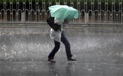 Женщина пытается удержать зонт во время сильного ветра и ливня в Пекине 18 мая 2010 года. Ураганный ветер и холода в Краснодарском крае оставили без энергоснабжения 250.000 человек, сообщила пресс-служба энергокомпании Кубаньэнерго, управляющей распределительными сетями региона. REUTERS/David Gray