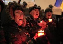 <p>Demonstrators shout slogans during snowfall during a protest against the government at Universitatii square in central Bucharest January 26, 2012. REUTERS/Radu Sigheti</p>