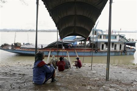 Workers pause after loading a Chinese boat at the Thai Mekong river port of Chiang Saen in the Golden Triangle region where the borders of Thailand, Laos and Myanmar meet January 14, 2012. REUTERS/Sukree Sukplang