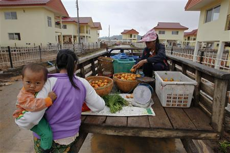 A woman buys fruit in a new village that Chinese company Jin Mu Mian claimed it built for Lao people displaced by the building of the Kings Roman casino complex along the Mekong river bordering Thai-Laos opposite Sop Ruak January 14, 2012.  REUTERS/Sukree Sukplang
