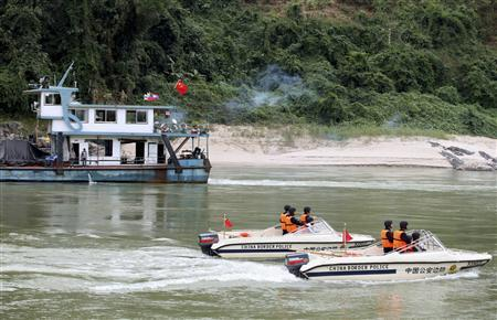 Chinese policemen in patrol boats accompany a cargo vessel (L) along the Mekong River after departing from Guanlei port, Xishuangbanna Dai Autonomous Prefecture, Yunnan province, December 10, 2011.  REUTERS/China Daily/Files