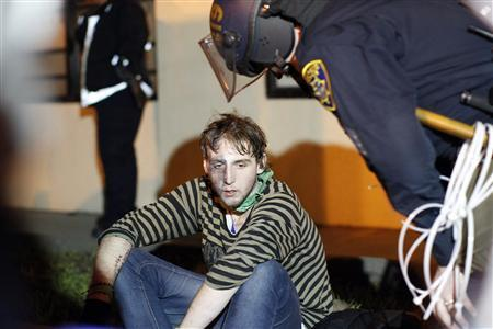 An Occupy Oakland demonstrator waits for medical assistance during a mass arrest outside a YMCA after a day-long demonstration in Oakland, California January 28, 2012.    REUTERS/Stephen Lam