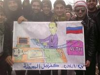 Демонстранты в сирийском Кафранбеле, близ Идлиба, держат карикатуру в ходе акции протеста против правления Башара Асада. Фото от 27 января 2012. Решение многомесячного политического кризиса в Сирии увязло в дипломатических спорах - США пытаются преодолеть сопротивление России, опасающейся, что Запад хочет избавить Сирию от неурядиц по уже опробованному в Ливии сценарию военного вторжения. REUTERS/Handout