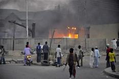 People watch as smoke rises from the police headquarters after it was hit by a bomb in Nigeria's northern city of Kano January 20, 2012.  REUTERS/Stringer