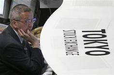 Работник Токийской фондовой биржи следит за ходом торгов, 2 февраля 2012 года. Токийская фондовая биржа TSE столкнулась с крупнейшими более чем за 6 лет техническими проблемами в четверг ночью по московскому времени, в результате которых были остановлены торги по 241 инструменту, включая акции Sony Corp, Komatsu Ltd и Hitachi, что вызвало гнев трейдеров. REUTERS/Kim Kyung-Hoon (JAPAN - Tags: BUSINESS)