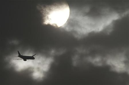 A passenger aircraft is silhouetted against the rising sun after its take-off at the airport in New Delhi March 29, 2011. REUTERS/B Mathur