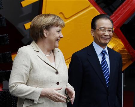 German Chancellor Angela Merkel (L) smiles next to Chinese Premier Wen Jiabao in front of a tunnelling system during their visit to a plant of Herrenknecht Tunnelling Equipment Co Ltd in Guangzhou February 3, 2012. REUTERS/Bobby Yip