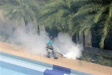 A worker 'fogs' in the public area of a private condominium in Singapore, May 24, 2006.  REUTERS/John Voos