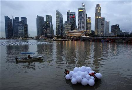 Workers transport newly penned ''wishing spheres'' to the centre of Marina Bay in Singapore December 20, 2011. REUTERS/Tim Chong/Files