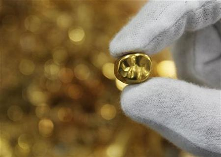 An employee displays a gold tooth at a shop that purchases gold in the Ginza district of Tokyo August 23, 2011.    REUTERS/Toru Hanai