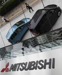 Пешеходы отражаются в зеркальной поверхности здания штаб-квартиры Mitsubishi Motors Corp в Токио, 13 июня 2011 г. Японская Mitsubishi Motors Corp решила в конце этого года остановить производство на своем единственном в Западной Европе заводе, в Нидерландах, после снижения продаж на европейском рынке. REUTERS/Yuriko Nakao