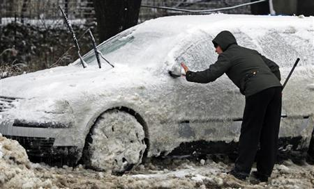 A woman cleans her frosted vehicle in Bucharest, February 5, 2012.  REUTERS/Radu Sigheti