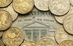 Монеты в 1 австралийский доллар на долларовой банкноте в Сиднее, 27 июля 2011 года. Австралийский доллар достиг абсолютных максимумов во вторник утром в паре с евро и полугодовых пиков - против валюты США после решения Резервного банка Австралии сохранить учетную ставку на уровне 4,25 процента годовых, тогда как примерно половина рынка ожидала её понижения до 4,00. REUTERS/Tim Wimborne