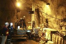Рабочие стоят возле оборудования на месторождении Кумтор в Киргизии, 28 июня 2011 г. Работа на критически важном для экономики Киргизии золотодобывающем месторождении Кумтор приостановлена из-за организованной профсоюзом забастовки, сообщил вечером в понедельник владелец прииска, канадская компания Centerra Gold Inc. REUTERS/Vladimir Pirogov