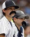 """Поклонники New York Yankees с накладными усами смотрят игру с Tampa Bay Rays в Нью-Йорке, 9 июля 2008 г. В американском штате Мэн пройдет первый в мире """"усатый"""" фестиваль фильмов, который состоится в рамках ежегодного праздника Stache Pag, посвященного растительности на мужских лицах.  REUTERS/Ray Stubblebine"""