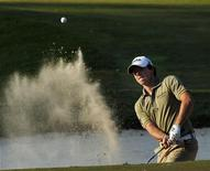 Rory Mcllroy of Northern Ireland hits from a bunker on the 18th green after winning the Hong Kong Open golf tournament December 4, 2011. REUTERS/Tyrone Siu