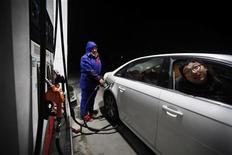 Человек заправляет автомобиль на АЗС в Шанхае, 7 февраля 2012 г. Китай увеличивает закупки нефти в Саудовской Аравии, России, Австралии и Западной Африке, чтобы компенсировать сокращение поставок из Ирана, от которого Пекин требует снижения цен. REUTERS/Aly Song