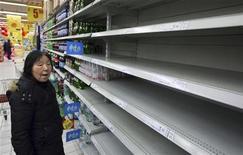 Женщина стоит перед пустыми товарными полками, где раньше стояли бутылки с питьевой водой в супермаркете  в китайской провинции Цзянсу, 7 февраля 2012 года. Власти Шанхая обеспокоены химическим загрязнением реки Янцзы - основного источника воды самого густонаселенного города Китая, написала в среду газета Shanghai Daily. REUTERS/China Daily