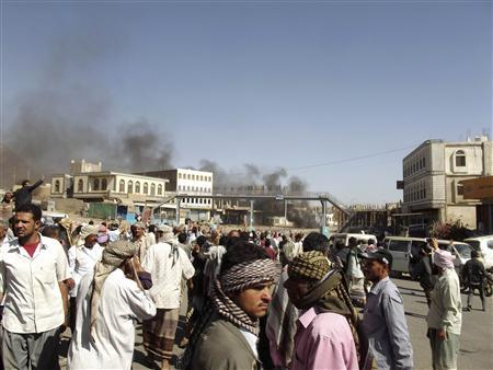 People gather as smoke rises from the site of clashes between government forces and anti-election protesters in the southern Yemeni city of Dalea February 9, 2012.  REUTERS/Stringer