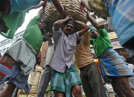 Workers prepare to carry a packed basket of vegetables at a wholesale vegetable market in Kolkata January 19, 2012. REUTERS/Rupak De Chowdhuri/Files