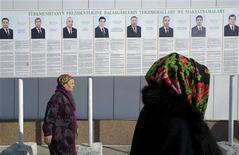 """Жительницы Ашхабада проходят мимо стенда с портретами кандидатов в президенты Туркмении 7 февраля 2012 года. Подданные называют его Аркадаг (""""Покровитель""""). Он президент, премьер-министр и верховный командующий; он бесспорный лидер страны, в недрах которой сосредоточены четыре процента мировых запасов газа. REUTERS/Aman Mehinli"""