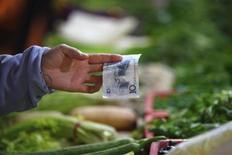 Продавец держит банкноту в 10 юаней, пока покупатель платит за овощи на рынке в Шанхае, 9 ноября 2011 г. Объем внешней торговли Китая резко сократился в январе 2012 года из-за существенного снижения импорта, что, по мнению некоторых аналитиков, порождает опасения о более сильном замедлении второй по величине экономики мира и необходимости мер по ее стимулированию, несмотря на высокую инфляцию. REUTERS/Aly Song