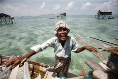<p>A sea gypsy smiles before she leaves to fish in her neighbourhood in Sulawesi Sea in Malaysia's state of Sabah on the Borneo island February 17, 2009. REUTERS/Bazuki Muhammad</p>