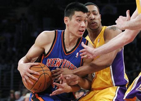 Newly acquired New York Knicks guard Jeremy Lin (L) is fouled by Los Angeles Lakers' Andrew Goudelock (R) during second half of an NBA basketball game in Los Angeles December 29, 2011. REUTERS/Danny Moloshok