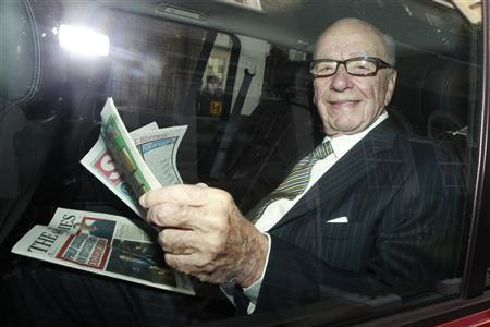 News Corporation CEO Rupert Murdoch holds a copy of The Sun and The Times as he is driven away from his flat in central London July 11, 2011. REUTERS/Luke Macgregor/Files
