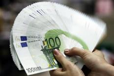 Сотрудница банка в Тайбее держит веер из купюр по 100 евро, 10 мая 2010 года. Евро вырос в понедельник после того, как парламент Греции одобрил закон о мерах экономии, который приближает страну к получению необходимых средств, однако рыночные игроки опасаются появления новых препятствий. REUTERS/Pichi Chuang