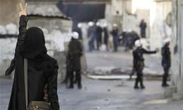 Участница антиправительственных акций протеста показывает полицейским знак победы во время беспорядков в деревне Санабис, к западу от Манамы, 12 февраля 2012 года. В Бахрейне возобновились ожесточенные столкновения между оппозиционерами и полицией в канун годовщины массовых демонстраций 14 февраля. В ответ король Бахрейна обвинил протестующих в поддержке Ирана и его духовного лидера Али Хаменеи. REUTERS/Hamad I Mohammed