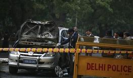 Полиция осматривает поврежденный взрывом автомобиль израильского посольства в Дели 13 февраля 2012. В Дели в понедельник сработало заложенное вблизи израильского посольства взрывное устройство, тогда как бомбу в дипмиссии Израиля в Тбилиси удалось обезвредить, сообщил израильский МИД. REUTERS/Parivartan Sharma