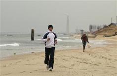 O corredor palestino Bahaa al-Farra treina na praia, na Cidade de Gaza.  O atleta de 19 anos, que  treina durante três horas diárias, prepara-se para a Olimpíada de Londres. 30/01/2012  REUTERS/Mohammed Salem