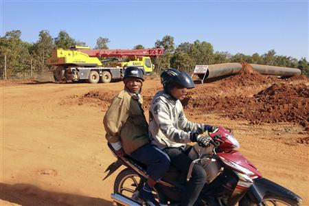 People drive on a moped at the construction site for a pipeline which will transport Myanmar gas into China, outside of the northeastern Myanmar town of Pyin Oo Lwin January 23, 2012. REUTERS-Staff