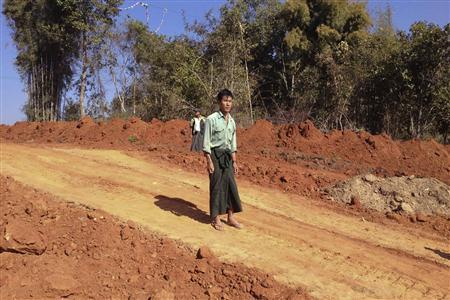 Farmer U Thant Lwin stands on the site of his old paddy field, which has been ripped apart to make way for a gas pipeline to China, near the northeastern town of Pyin Oo Lwin January 23, 2012. Picture taken January 23, 2012. REUTERS-Staff