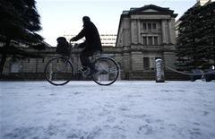 Мужчина проезжает на велосипеде мимо здания Бвнка Японии в Токио, 24 января 2012 года. Банк Японии смягчил монетарную политику во вторник, расширив скупку активов в связи с усилением политического давления к более решительным действиям ради сдерживания дефляции и облегчения экономических последствий сильной иены. REUTERS/Toru Hanai (JAPAN - Tags: BUSINESS)