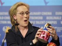 "Meryl Streep reacts as she looks at a matryoshka doll, decorated with a portrait of former British Prime Minister Margaret Thatcher, she received as a gift from a Russian journalist during a news conference to promote the movie ""The Iron Lady"" at the 62nd Berlinale International Film Festival in Berlin February 14, 2012.    REUTERS/Morris Mac Matzen"